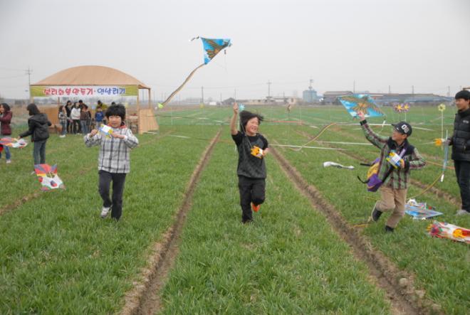 오산면 밀·보리밭 축제에 참가한 새싹들이 연을 날리며 푸른 초원으로 변한 보리밭을 신나게 달리고 있다