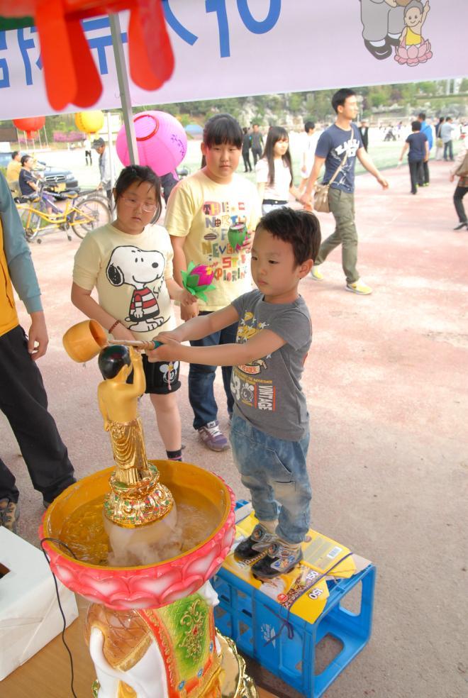 연등축제에 참가한 한 어린이가 아기부처 머리에 관불(灌佛)을 하고 있다.
